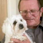Disability pensioner Allan Flanagan gives his dog Lucy a cuddle after she chased burglars from his home.